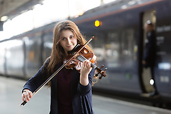 © Licensed to London News Pictures. 01/03/2016. London, UK. Two exceptional teenage violin prodigies, Coco Tomita, 13 (not pictured) and Louisa Staples, 15, who are competitors in the world's leading competition for young violinists, the Menuhin Competition London 2016 (which takes place on 7-17 April 2016), surprise commuters as they perform on the platform at St Pancras International Station in London. Photo credit : Vickie Flores/LNP