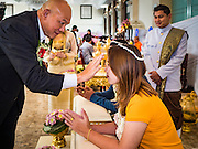 "14 FEBRUARY 2017 - BANGKOK, THAILAND: A couple completes their wedding with a traditional Thai blessing in the Bang Rak district in Bangkok. Bang Rak is a popular neighborhood for weddings in Bangkok because it translates as ""Village of Love."" (Bang translates as village, Rak translates as love.) Hundreds of couples get married in the district on Valentine's Day, which, despite its Catholic origins, is widely celebrated in Thailand.      PHOTO BY JACK KURTZ"