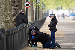 © Licensed to London News Pictures. 11/05/2021. London, UK. Police officers search a section of bollards on the Mall ahead of the state opening of Parliament . Photo credit: George Cracknell Wright/LNP
