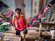 11 JULY 2017 - BANGKOK, THAILAND:  A woman swings in a hammock in front of her home in a community built over the Chao Phraya River south of Krung Thon Bridge. The residents of the community expect to be evicted and their homes destroyed to make way for the city's plan to build a 14 kilometer long (22 mile) riverfront promenade. Thousands of families are expected to be evicted to accommodate the promenade. The riverside communities, built on stilts over the water, are prone to flooding and the city has been trying to control them for years. The houses are the only affordable housing for available to some of the poorest people in Bangkok.     PHOTO BY JACK KURTZ