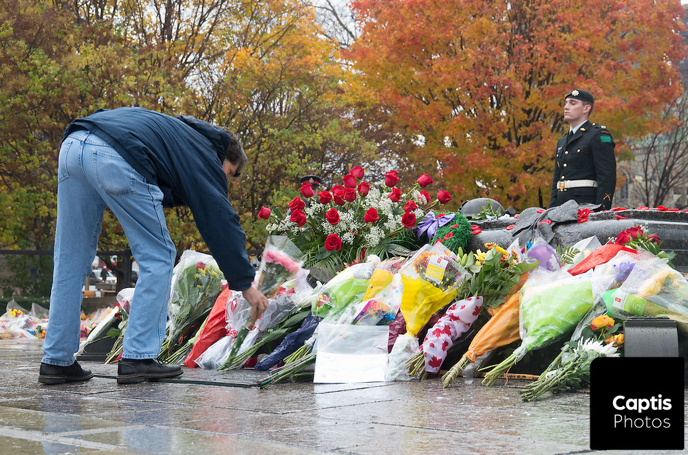 A man places flowers on the cenotaph at the National War Memorial three days after the fatal shooting of Cpl. Nathan Cirillo. October 25, 2014.