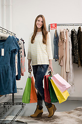 Portrait of young woman holding shopping bags, smiling