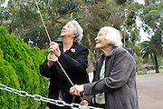 Nell O'Grady (left) and Jan Yurisich (right) raise the Western Australian State flag.