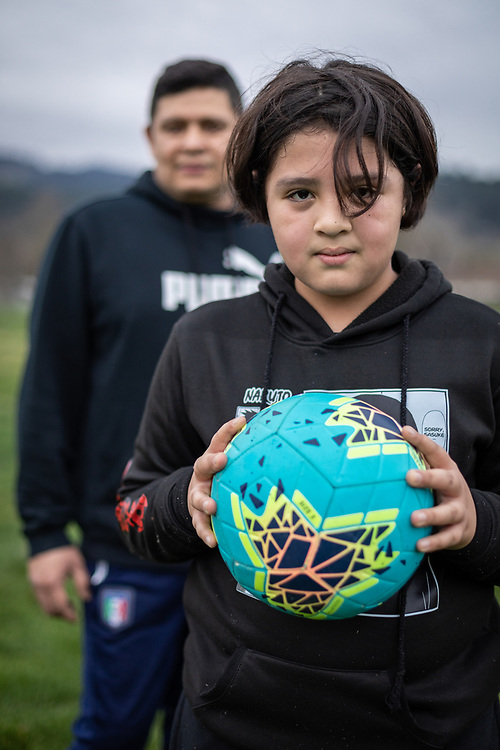"""""""My wife lost her job early on.  Luckily, I am on salary.  We are worried that everything could get much worse.  My son and I try to get out and kick the ball around whenever we can. We are trying to stay healthy.""""  Sous-chef Ivan Lucas and his ten year old son, Andrew, end an afternoon of soccer practice behind the Calistoga High School."""