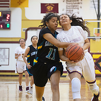 Tohatchi Cougar Cameron Tsosie (20) drives to the basket and is fouled by Navajo Prep Eagle Hailey Martin (11) at Tohatchi High School Thursday night in Tohatchi.
