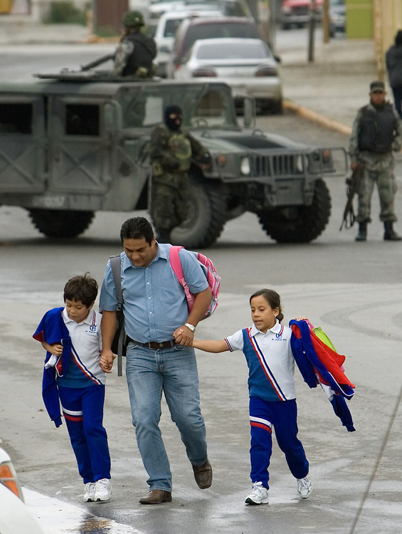 Reynosa, Tamaulipas - 17 Feb 2009 - .A Reynosa man picks up his children from Escuela Primaria Carrillo Puerto after 5 people were killed in a shootout involving Mexican Federal Police on Tuesday morning..Photo by Alex Jones / ajones@themonitor.com