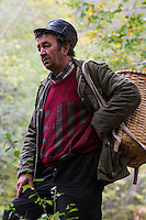 Romanian man with woven basket on his back for carrying edible tree mushrooms - mostly from Common beech (Fagus sylvatica) - picked in the forest close to Baile Herculane, Caras Severin, Carpathians, Romania.