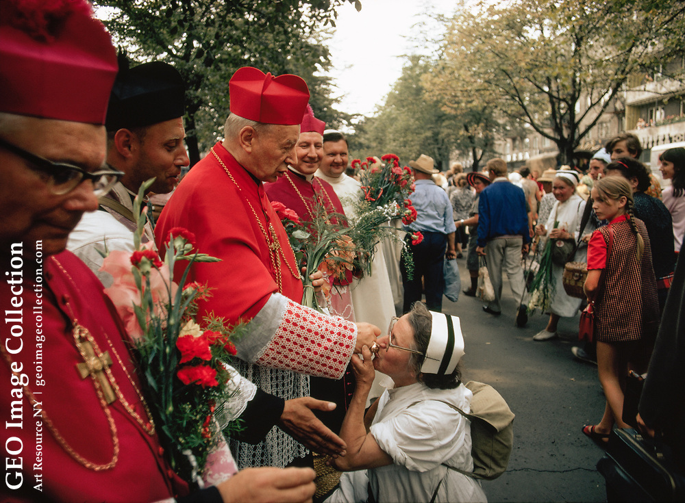 A nun kneels and kisses the ring of a Catholic cardinal.