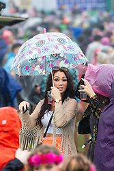 © Licensed to London News Pictures . 07/06/2014 . Heaton Park , Manchester , UK . A woman with a bright umbrella wends her way through the crowds . The Parklife music festival in Heaton Park Manchester following heavy overnight rain . Photo credit : Joel Goodman/LNP