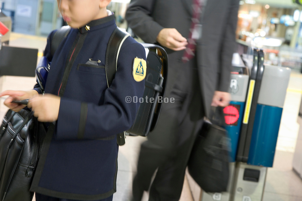 a young elementary school child in uniform coming out of the subway with his father in office clothing Japan
