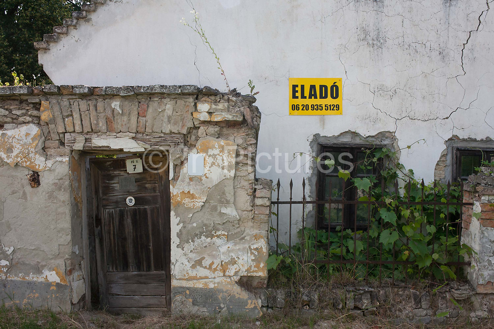 An abandoned, crumbling and riuned house with its accompanying land, has the Hungarian word Elado - meaning For Sale - on a cracked exterior wall in a village of population 178 on 26th June 2016, in Bakonygyriot, Gyor-Moson-Sopron, Hungary. Its doorway is warped and leaning, the brickwork is crumbling and in a general poor condition. As the old pass away, so properties in the rural backwaters of Hungary fail to regenerate a younger population and old, communist-era buildings are falling into disrepair.