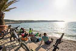 Bikers sitting at shore of beach and relaxing