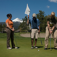 Chad Jones putts on a green at Big Sky Golf Course in Big Sky, Montana while Shane Knowles & Lindsey Mitchell watch.