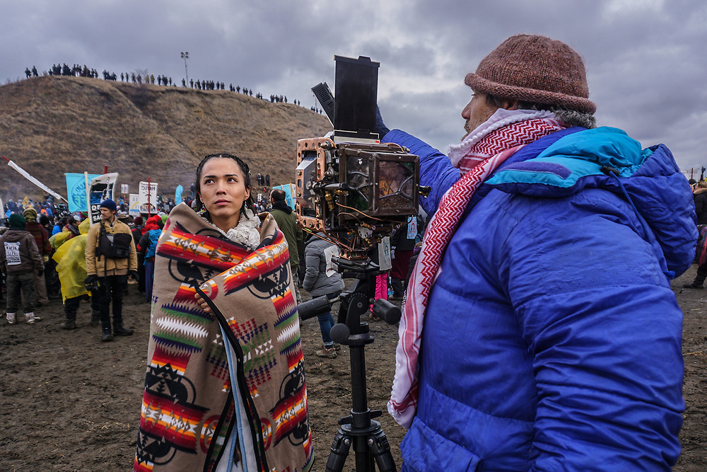 """""""Us & Them"""" photo shoot during a battle between the Standing Rock Sioux Water Protectors and the Sheriffs Dept, National Guard, and Dakota Access Pipeline hired guns. <br /> <br /> The woman in the photo is from the Navajo Nation."""