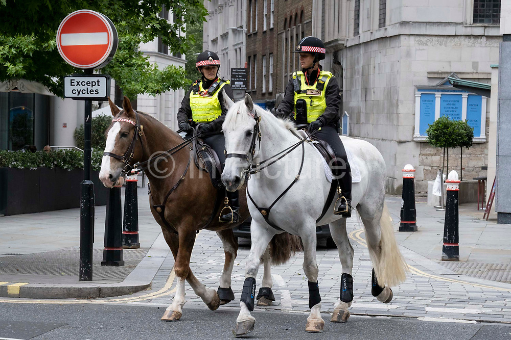 Two Women Officers with the City of London Police, ride their horses on a routine daily patrol through the City of London, the capitals financial district, on 22nd June 2021, in London, England.