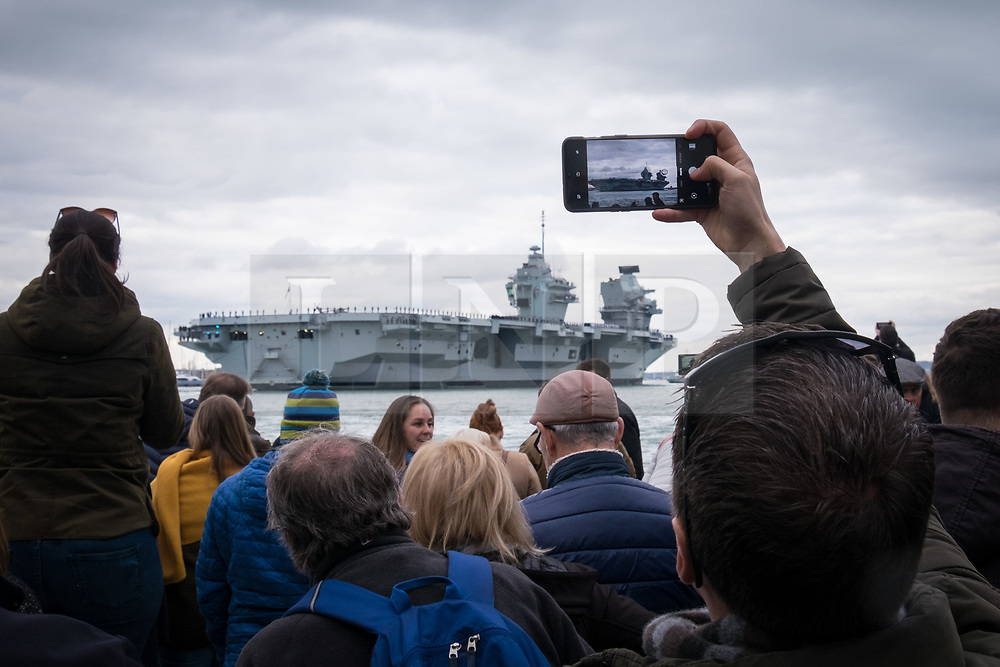 © Licensed to London News Pictures. 16/11/2019. Portsmouth, UK.  A man taking a photo as HMS Prince of Wales, the Royal Navy's second Queen Elizabeth-class aircraft carrier, sails into Portsmouth Naval Base for the first time this afternoon, 16th November 2019. The £3.1 billion warship has been undergoing eight weeks of sea trials in the Moray Firth. Photo credit: Rob Arnold/LNP