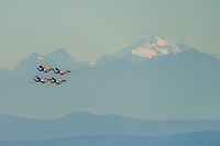 Four Blue Angels fly in front of the Cascade Mountains
