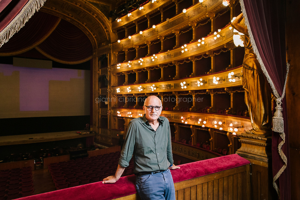 """PALERMO, ITALY - 1 OCTOBER 2019:  Ludovico Einaudi (63), composer of the opera """"Winter Journey"""", poses for a portrait during the rehearsal  at the Teatro Massimo in Palermo, Italy, on October 1st 2019.<br /> <br /> Co-produced by the Teatro Massimo in Palermo and the Teatro San Carlo in Naples, """"Winter Journey"""", which has its world premiere here on Friday, tells the story of desperate migration from troubled, war-torn countries towards Europe, in its indifference and rejection. <br /> <br /> """"It is a journey towards a country where they will find hostility, a cold welcome or perhaps no welcome at all, to a place where there is a winter of the soul,"""" said the Italian pianist and composer Ludovico Einaudi, who wrote the score of the opera to a libretto by the Irish novelist and critic Colm Tóibín. """"It is a journey to a hostile world, without points of reference, in which your soul can die,"""" he said. <br /> <br /> The story is told from the perspective of three characters – a man from an unnamed country moving from hardship to hardship on his way to Europe in search of a better life – and the woman and child he has left behind. The choir serves as a Greek chorus while a politician (played by an actor) intervenes intermittently with refrains that will be familiar to many European ears: """"The boat cannot dock at our port"""", """"Why should we deal with this problem"""" and """"We do not want strangers on our streets."""""""