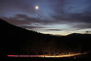 Salisbury Mills, New York  - The moon shines in the sky above Schunnemunk Mountain as a car drives along Otterkill Road at on Nov. 27, 2011.