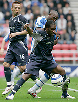 Photo: Dave Howarth.<br />Wigan Athletic v Bolton Wanderers. The Barclays Premiership. 02/10/2005. Jay Jay Okocha holds off Jason Roberts