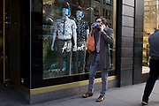 Man on smartphone and with coffee, is occupied by a display of eccentric mannequins in diving masks and snorkels. Multitasking with a smartphone, holding a bag and drinking a coffee, the man proves he can do many things at once but is overshadowed by the weird display of two models behind him, in their strange headwear. The shop is Ted Baker plc, a British luxury clothing retail company. It is listed on the London Stock Exchange and is a constituent of the FTSE 250 Index. Its founder and CEO, Ray Kelvin, started his first store in March 1988 and it now has stores and outlets in the rest of Europe, United States of America, Canada, Australia, Asia, China and the Middle East.