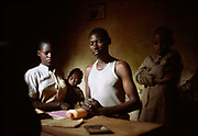 Narcisse, who is HIV positive and the president of his local AIDS Association - Girimpuhwe ('Have compassion') - prays with his family at home at dawn before they start work in the fields. Kibileze, Rwanda.