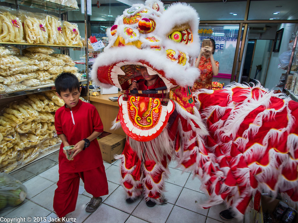 """19 FEBRUARY 2015 - BANGKOK, THAILAND: A lion dance troupe solicits donations in a Chinese grocery store on Chinese New Year in the Chinatown district of Bangkok. 2015 is the Year of Goat in the Chinese zodiac. The Goat is the eighth sign in Chinese astrology and """"8"""" is considered to be a lucky number. It symbolizes wisdom, fortune and prosperity. Ethnic Chinese make up nearly 15% of the Thai population. Chinese New Year (also called Tet or Lunar New Year) is widely celebrated in Thailand, especially in urban areas that have large Chinese populations.    PHOTO BY JACK KURTZ"""