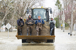 People are given a ride in a backhoe as they make their way home along a flooded street in the the town of Rigaud, Quebec, Canada., west of Montreal, Monday, May 8, 2017, following flooding in the region. Photo by Graham Hughes /The Canadian Press/ABACAPRESS.COM