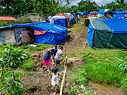 29 JANUARY 2018 - SANTO DOMINGO, ALBAY, PHILIPPINES: A woman and her daughter leave an impromptu camp in Santo Domingo for people evacuated from their homes because of the Mayon volcano. Many of the shelters in Santo Domingo are filled beyond capacity and people are sleeping tents and huts along the roads.  Mayon volcano's eruptions continued Monday. At last count, more 80,000 people have been evacuated from their homes of the slopes of the volcano and are crowded into shelters in communities outside of the danger zone.    PHOTO BY JACK KURTZ