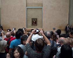 Crowds of tourists looking at Mona Lisa painting in gallery at The Louvre in Paris France
