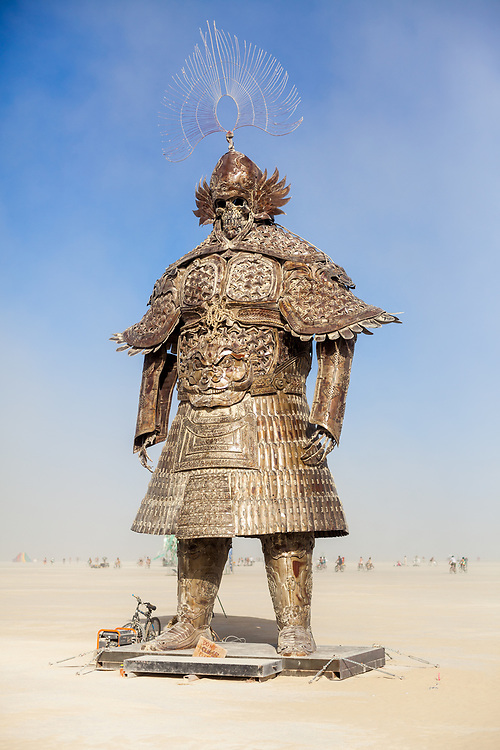 Desert Guard by: Lu Ming from: Beijing, China year: 2018<br /> <br /> Fenghaizhen's design is inspired by the armor of Genghis Khan whose Mongolian empire ruled China during a part of the 14th century. The Mongolian army resisted their enemies' aggression thanks to Genghis Khan's military tactics, a strong system of weapons and their special armor. It had a very primitive but effective shock absorbing and impact diverting system. This art piece enlarges the armor to a height of 15 metres weighing 10 tons and embedded the soul of a Mongolian warrior. It wants to remind everyone, that we must never use artificial intelligence for war. Otherwise, humanity creates weapons that kill us. We hope that this warrior makes us realise that we shouldn't only worship technology, but also put restrictions in place. Contact: beijingburners@gmail.com