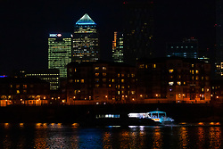 © Licensed to London News Pictures. 24/03/2020. London, UK. An empty Thames Clipper commuter boat travels on the River Thames as the top of One Canada Square is seen illuminated in blue next to the empty offices of banks and financial institutions in London's Canary Wharf financial district this evening. This has been done in recognition and appreciation of National Health Service (NHS) staff working in hospitals across the country during the ongoing COVID-19 coronavirus epidemic. Photo credit: Vickie Flores/LNP
