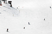 people on a large slope skiing down hill