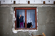 "The new built house of Rudolf (52) - his grandchildren playing on the window. The family is among those who joined the micro loan program in Rankovce. ""They and their son Rudo and three small grandchildren have never lived in their own home. They have been homeless or lived in a caravan without drinking water and electricity. Since the fall of communism Rudolf has not been able to get a permanent job. Rudolf's family has to survive on less than 2 euro per person a day, living only off social welfare and occasional jobs."" (ETP Slovakia)."