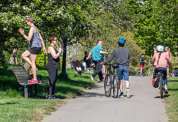 © Licensed to London News Pictures. 19/04/2020. London, UK. Two women exercise on a bench on a warm Spring day as Police patrol Primrose Hill enforcing lockdown rules on social distancing and exercise as Ministers urge councils to keep parks open to the public during lockdown. Photo credit: Alex Lentati/LNP