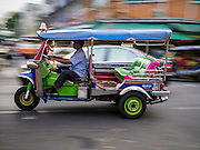 "17 MAY 2013 - BANGKOK, THAILAND:   A ""tuk-tuk,"" or three wheeled taxi, on Chakphet Road in front of the flower market in Bangkok. The Bangkok Flower Market (Pak Klong Talad) is the biggest wholesale and retail fresh flower market in Bangkok. It is also one of the largest fresh fruit and produce markets in the city. The market is located in the old part of the city, south of Wat Po (Temple of the Reclining Buddha) and the Grand Palace.   PHOTO BY JACK KURTZ"
