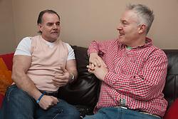 Two men talking on sofa.