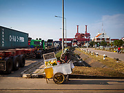 """12 FEBRUARY 2019 - SIHANOUKVILLE, CAMBODIA: A fruit vender who serves drivers going into the Sihanoukville port. There are about 50 Chinese casinos and resort hotels either open or under construction in Sihanoukville. The casinos are changing the city, once a sleepy port on Southeast Asia's """"backpacker trail"""" into a booming city. The change is coming with a cost though. Many Cambodian residents of Sihanoukville  have lost their homes to make way for the casinos and the jobs are going to Chinese workers, brought in to build casinos and work in the casinos.       PHOTO BY JACK KURTZ"""