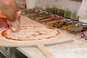 Stages of pizza preparation sprinkling ground yellow cheese on the pizza base