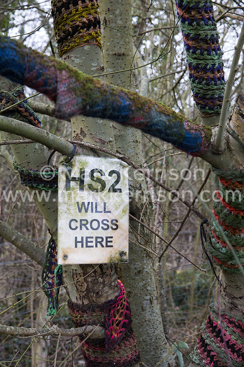 Wendover, UK. 20th February, 2021. A sign indicating the route of the HS2 high-speed rail link is pictured fixed to a tree wrapped in scarves close to the site of the Wendover Active Resistance Camp which is occupied by activists opposed to HS2 from HS2 Rebellion.