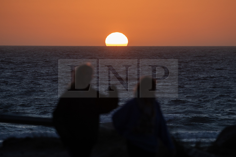 © Licensed to London News Pictures. 02/04/2020. Padstow, UK. Women walk past the sun setting over Constantine Bay on the north coast of Cornwall after a warm clear day. Warm weather is expected next week. Photo credit : Tom Nicholson/LNP