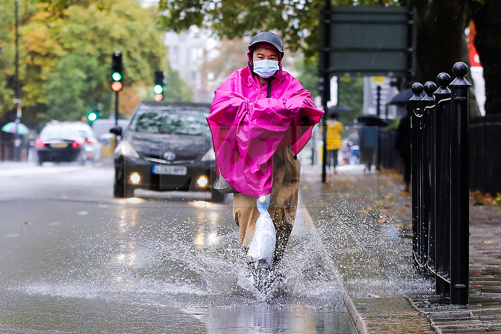 © Licensed to London News Pictures. 04/10/2020. London, UK. A woman wearing a face mask and raincoat rides her electric scooter through surface rainwater in north London, as Storm Alex brings heavy rain to large parts of the UK. The Met Office forecasts heavy rain and windy weather for the next of the day in the capital. Photo credit: Photo credit: Dinendra Haria/LNP