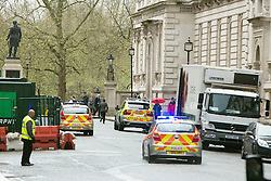 © Licensed to London News Pictures. 07/04/2014. London, UK. Armed Police arrest a man in King Charles Street today 7th April 2014. The street that runs between the Foreign Office and The Treasury, including an entrance to Downing Street has a search point at it's entrance. The man was led away to a waiting police van and officers were seen collecting evidence and an Adidas bag. . Photo credit : Stephen Simpson/LNP