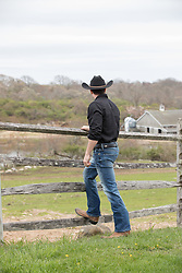 back of a cowboy looking out to a ranch