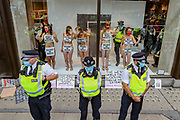Police form a line around H&M after Extinction Rebellion activists have glued themselves to the shop window of H&M in Oxford street in London on Wednesday, Sept 9, 2020. The activists are completely naked, except for strategically placed placards that made a statement about social and environmental injustice in the fashion industry. The signs read 'Fashion is F*cked, Rather Be Naked', 'Won't Wear Injustice, Rather be Naked' and 'Not Buying This Bullshit, Rather Be Naked'. Environmental nonviolent activists group Extinction Rebellion enters its 9th day of continuous ten days protests to disrupt political institutions throughout peaceful actions swarming central London into a standoff, demanding that central government obeys and delivers Climate Emergency bill. (VXP Photo/ Vudi Xhymshiti)