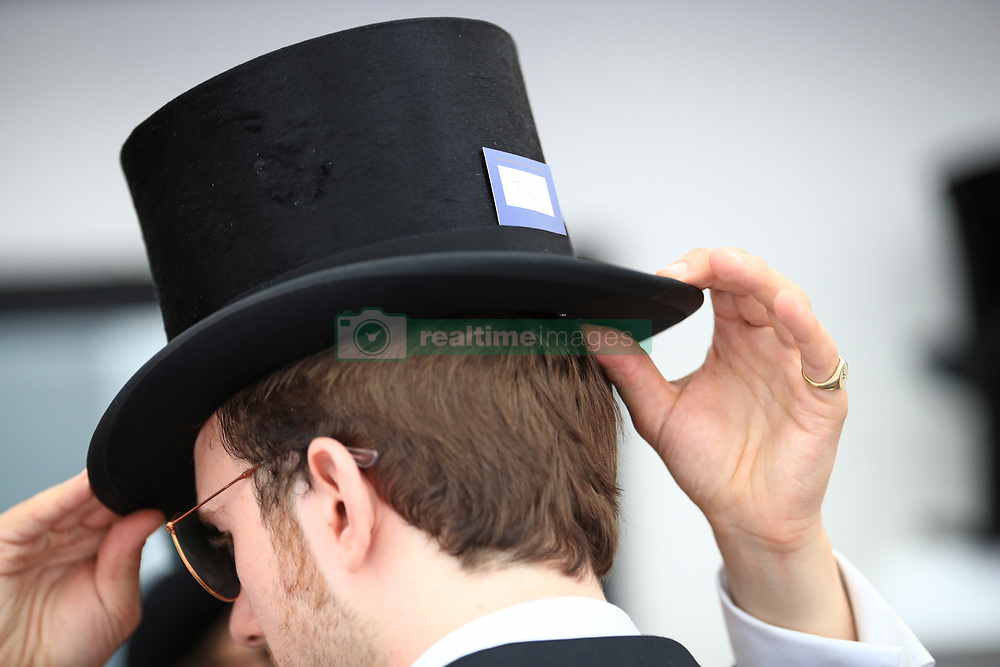 A racegoer is fitted for a hat during day two of Royal Ascot at Ascot Racecourse.