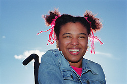 Young woman with Cerebral Palsy sitting in wheelchair outdoors in park laughing,