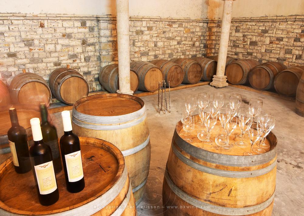 Oak barrels and bottles and glasses set up for a tasting. Cobo winery, Poshnje, Berat. Albania, Balkan, Europe.