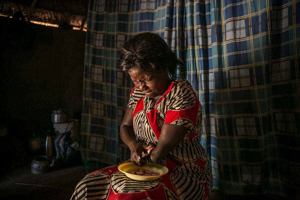 Margaret squints her eyes as she cuts an onion in her hut in Gulu. She was abducted at the age of 11 in Acholi-bur village and was assigned to a commander two years later who had 13 wives. She also started a military training at that time and spent eight years as a soldier.