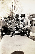 adult men posing with crying toddler 1930s